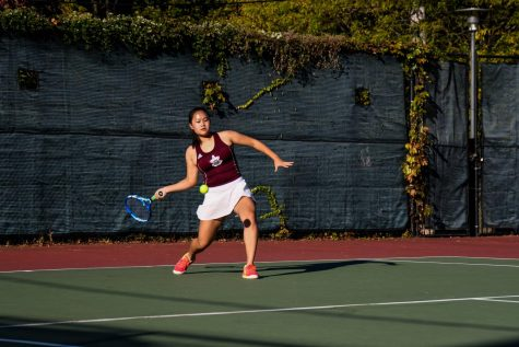 Sophomore Corona Chen, focused, prepares to swing her racket at the ball in a home match against Lake Forest.