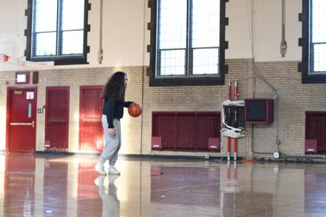 Sophomore Maya Atassi dribbles the ball at a practice in Sunny Gym last season Feb. 19. With the status of winter sports in doubt, the gym may remain empty for a while longer.