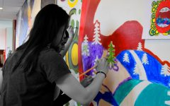 Students paint a mural at last year's Artsfest in the hallway between the high school building and Gordon Parks Arts Hall.