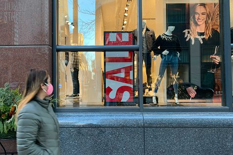 A shopper walks along Chicago's North Michigan Avenue past a sign for a Black Friday sale.