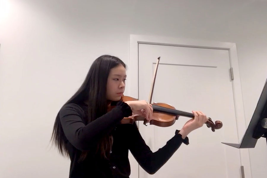 Violin in hand, sophomore Amelia Zheng concentrates on her virtual audition for the Illinois All-State Orchestra.