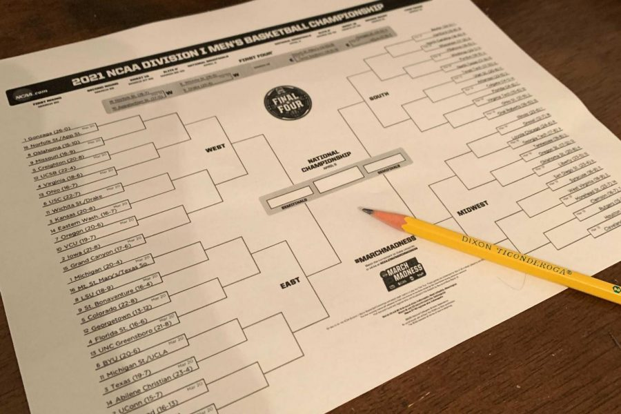 An unfilled NCAA Men's Tournament bracket lies on a table with a pencil at hand. Many students filled out brackets similar to this one by picking the winners of each matchup and moving them into the empty space in the next round.