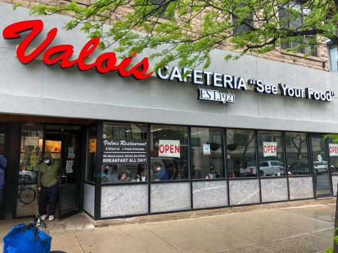 """TAKEOUT. A customer exits the Valois storefront on May 19. Many longtime customers of Valois have gotten takeout there during the pandemic. """"They actually already had a set-up where before the pandemic you could get take-out,"""" said Seth Richardson, a customer for 20 years."""