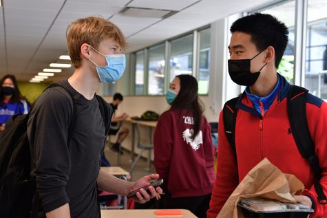 "Juniors Andrew Swinger and Todd Hao converse during lunch May 10. Andrew found the return with 9-11 graders different but appreciated seeing familiar faces. ""At the end of the school day, walking through that giant mob of people in the lobby was something I"