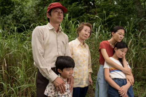 Youn Yuh-jung stares into the distance with her family on either side.