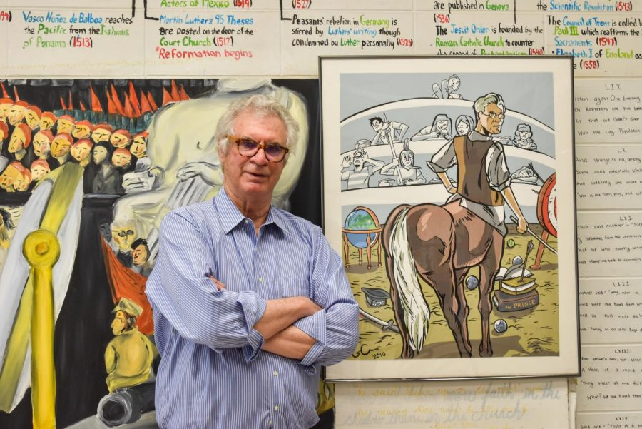 """Chris Janus poses in front of murals that students painted for his AT Modern European History course in C125. """"It felt good to have a physical example of the work we did in class,"""" Mr. Janus said. """"It adds character and unique stories to each room."""""""