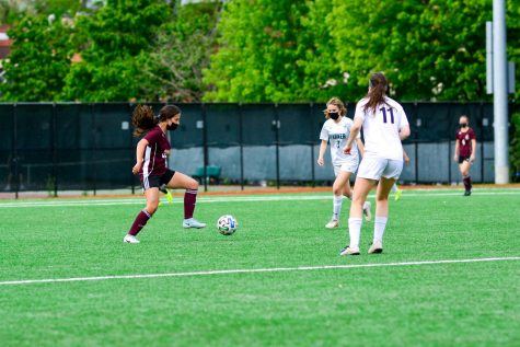 Junior Carly Penn passes between two players from Francis Parker on May 21. After a 4-0 win, the girls won the Independent School League title.
