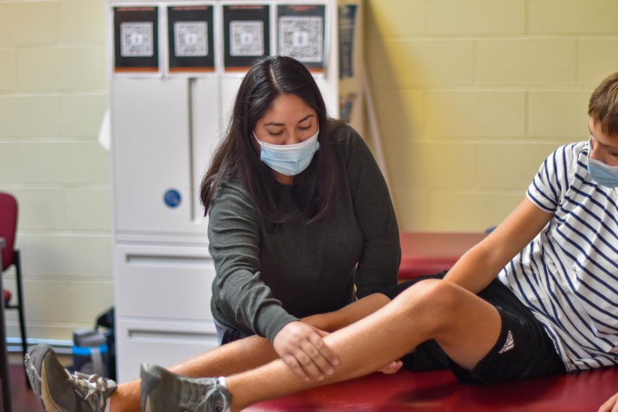 New+athletic+trainer+Breanna+Lewenthal+examines+an+athlete+in+the+fitness+center.+