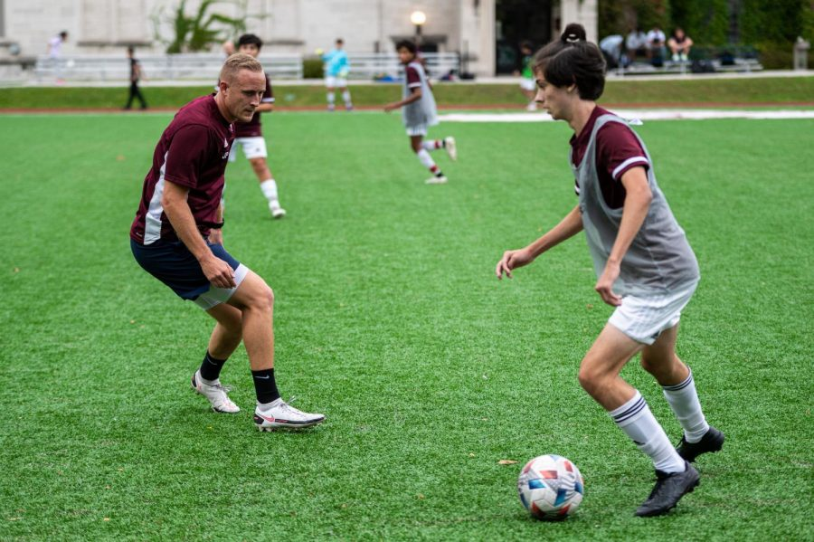 Soccer coach Josh Potter plays with junior Milo Jarard during a practice on Sept. 21. Mr. Potter recently received two awards from his alma mater.