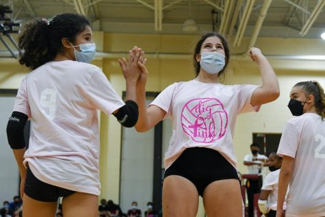 Sophomore Santana Romero, left, subs into the game for junior Audrey Matei on Oct. 20. For the annual Dig Pink game against DePaul College Prep, the volleyball team raised over $2,500 in donations to the Side Out Foundation.