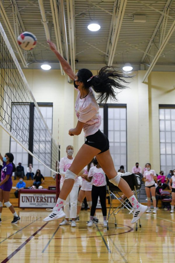 During warm-ups before the game against DePaul College Prep, Ariana Vazquez spikes a ball over the net.
