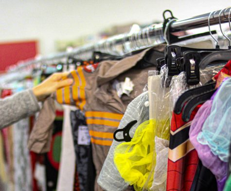 A costumer browses through a rack of Halloween costumes set out for the season at a Salvation Army.